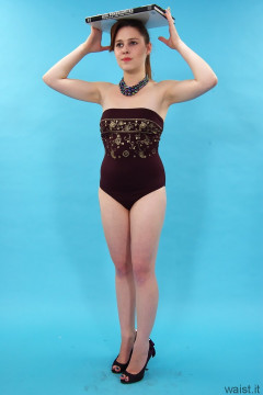 Lora in maroon and gold one-piece swimsuit repeating her grandmothers posture exercises