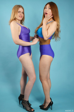2015-12-11 Chelskii and Laura in purple lycra one-piece swimsuits doing tummy exercises with tight leather corset belt to nip in the waist