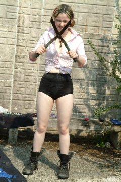 Annie in pink blouse zip-front girdle. gardening boots and shears