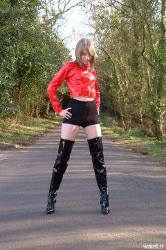 Carlie models red PVC jacket and black shiny pantie girdle worn as hot pants