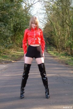 Carlie models red PVC jacket and black shiny pantie girdle worn as hot pants