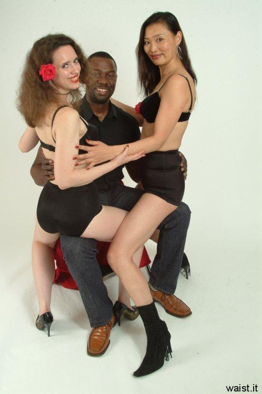 Chiara in black bra M&S brief pantie girdle and Moonlit Jane in black bra and tummy-control Skort, both sitting on Moonlit Jane's boyfriend.