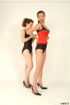 """""""Tummy in!"""" Chiara laces Moonlit Jane into tight Vollers corset."""