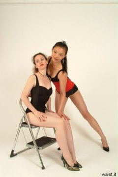Chiara and Moonlit Jane in black, tummy-control one-piece swimsuits worn as body-suits, Jane laced up all the way in a Red Vollers corset.