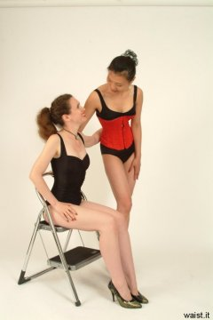 Chiara and Moonlit Jane in black, tummy-control one-piece swimsuits worn as body-suts, Jane laced up all the way in a Red Vollers corset.