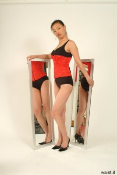 Moonlit Jane poses with mirrors in tight, red Vollers corset over fifties-style, tight, black, lycra, tummy-control one-piece swimsuit.