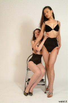 Chiara poses Moonlit Jane, both wearing bras and tight Maidenform waist-nipper girdles