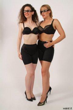 Chiara and Nikki in black multiway bras and shiny lycra long-leg pantie girdles worn as cycling shorts
