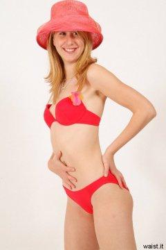 Dee in red bikini shows off flat tummy