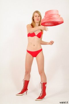 Dee in red bikini throws hat - Photo from Dee's retro swimwear and corsetry shoot, choreographed by Chiara 2005-09-30.