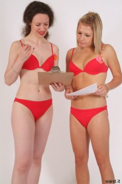 Chiara and Sara in red bikinis discussing shoot plan