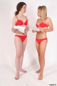Chiara and Sara in red bikinis discussing shoot plan