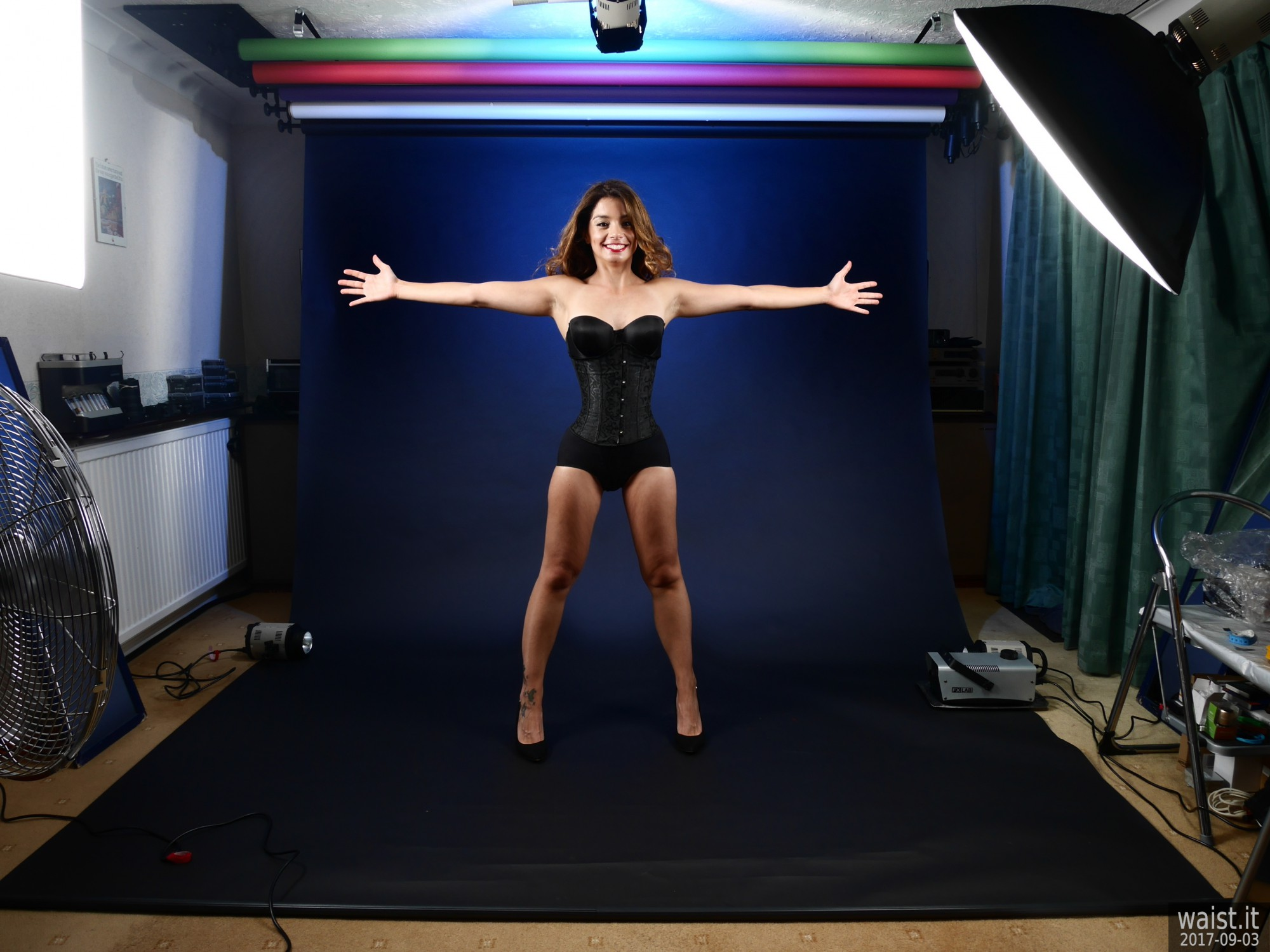 2017-09-03 Paula Soares showing off the studio in tightky-laced black underbust corset and tight black panelled pantie-girdle worn as hotpants