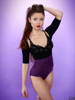 Charlene Joy in black bra and posture top, and purple high-waist control briefs worn as hotpants